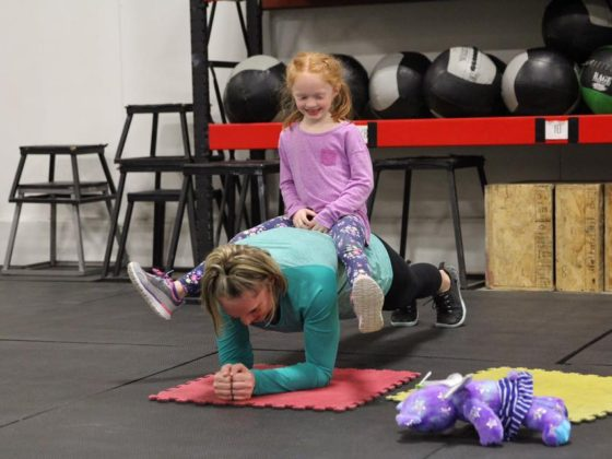 Mia helping Ellen out on her weighted planks.